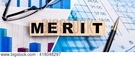 On The Bright Diagrams, Glasses, A Pen And Wooden Cubes With The Word Merit. Business Concept