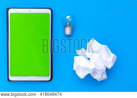 Tablet To Write Down A Person's Ideas Together With A Disposable Crumpled Paper And A Light Bulb As