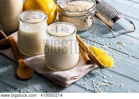 Appetizing Rice Pudding In Glass Jars With Cinnamon Sticks, Grains Of Rice, Milk And Lemons. Ready T