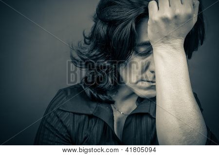 Dramatic  blue toned portrait of a woman suffering a headache or a strong depression