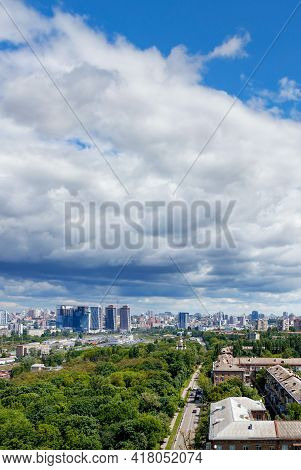 View From A Height Of The City Of Kiev In The Summer At Noon. A Green Park In The Foreground In An O