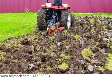 A Tractor With A Plow Plows An Agricultural Field In The Spring For Planting Potatoes. Plowing The L