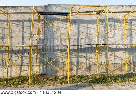 Extensive Scaffolding Providing Platforms For Work In Progress On A New Wall Block. Modern House Wal