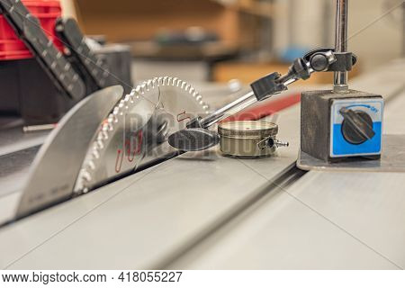 Dial Indicator. A Worker Adjusts A Scale Indicator To Align A Saw Blade In A Carpentry Workshop. Mai