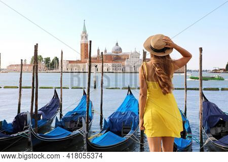 Young Female Traveler Enjoying Beautiful View On Venetian Channel With Gondolas Floating In Venice,