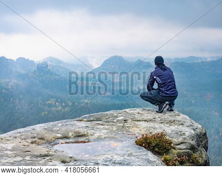 Man Sitting At The Peak Of A Mountain On A Foggy Morning.  Sit Squatting On The Peak Edge And Enjoyi
