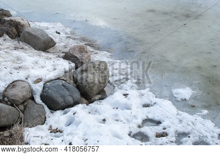 Melt Water Along The Rocky Shore Of The Pond. Remains Of Ice On The Surface Of The Pond.