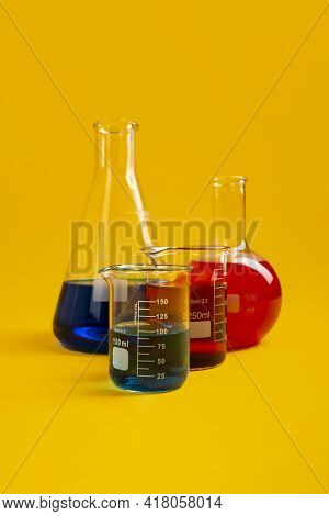 Flat Bottom Flask, Conical Flask And Two Berzelius Beaker Glasses Lay Against Mustard Yellow Backgro