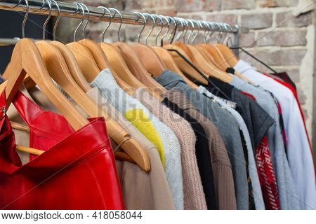 Second Hand Used Clothes On Hangers For Donation And Reselling. Garage Sale Or Economic Shopping Con