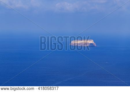 View Of The Sea And Coast On The Island Of Santorini Caldera In Greece. The Background Is A Blue Sky