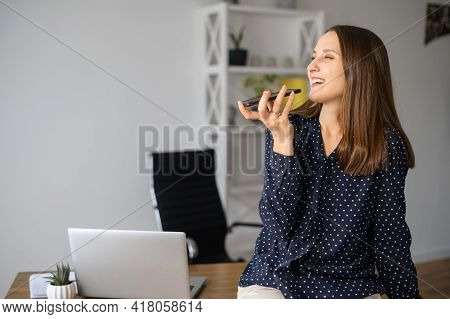 Smiling Female Employee Is Using Voice Assistant On The Smartphone, Young Woman Talking In The Mic O