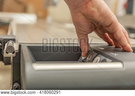Hand Presses The Button Turning On An Industrial Machine. Cutting Saw Blade. Switches For Controllin