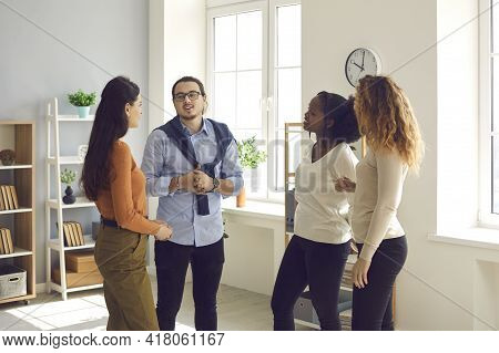 Group Of Young Diverse Business People Or Colleagues Talking In Informal Office Meeting