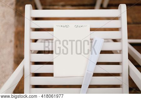 White Vertical Sheet Lies On A Wooden Chair Next To A Folded Fan
