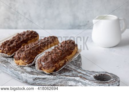 Three Eclairs On The Wooden Grey Board And Creamer On Grey Background