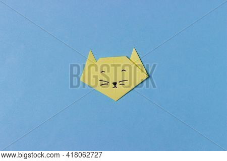 The Cat's Head Is Folded From Yellow Paper In The Technique Of Origami With Painted Eyes, Nose And M