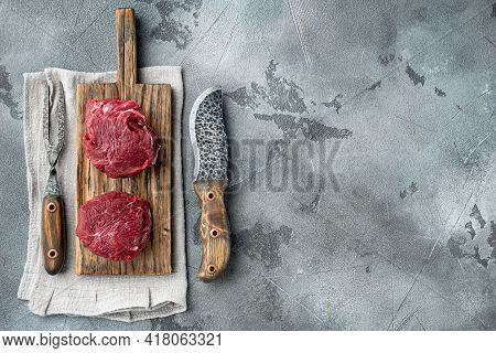 Raw Meat Beef Steak. Black Angus Prime Meat Set, On Wooden Cutting Board, On Gray Stone Background,