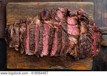 Sliced Grilled Meat Steak Rib Eye Medium Rare Set, On Wooden Serving Board, On Old Dark  Wooden Tabl