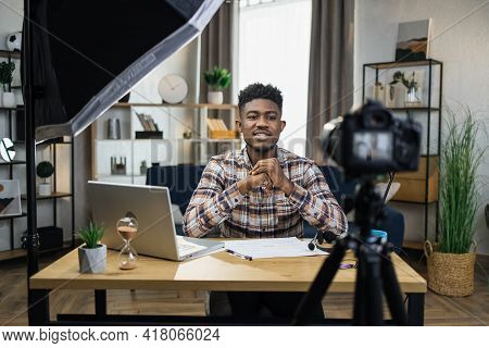 Handsome African Man Sitting At Table With Modern Laptop And Recording Video On Camera That Fixed On