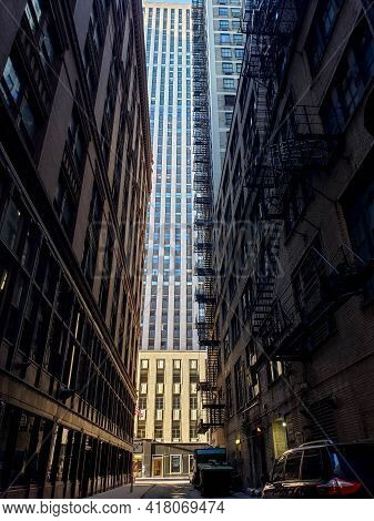 Chicago, Il April 12, 2021, Dark Back Alleyway With A Brightly Illuminated Art Deco Office Building