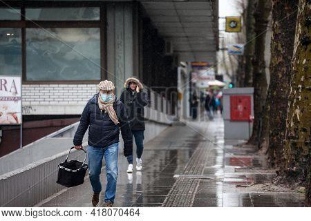 Belgrade, Serbia - April 3, 2021: Old Senior Man Wearing A Respiratory Face Mask Walking In The Stre