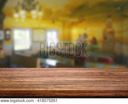 Empty Wooden Table With Blurry Image Of Coffee Shop Or Cafe Restaurant In Background For Product Sho