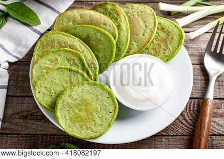 Pancakes With Spinach And Sour Cream On A Wooden Table. Gluten Free Spinach Pancakes Recipe