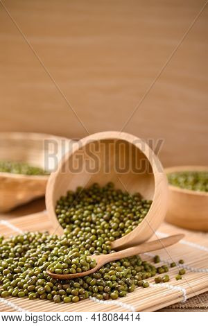 Pile Of Mung Bean Seeds In A Wooden Spoon And Bowl, Food Ingredients In Asian Cuisine And Produce Mu