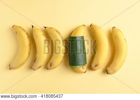 Group Of Ripe Banana Fruit And One Banana Wrapped By Banana Leaf On Yellow Background, Difference Co