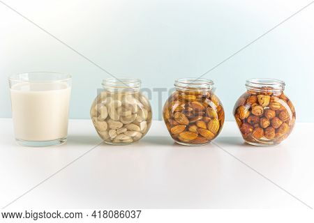 Process Of Soaking Various Nuts: Almonds, Hazelnuts, Cashew In Water To Activate And Glass Of Vegeta