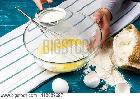 Womens Hands Sift Flour Through A Sieve. Dough Preparation Process. Kneading Pancake Dough.