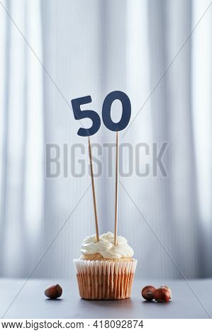 Homemade Vanilla Anniversary Cupcake With Creamy Topping And Number 50 Fifty With Hazelnuts Nearby A
