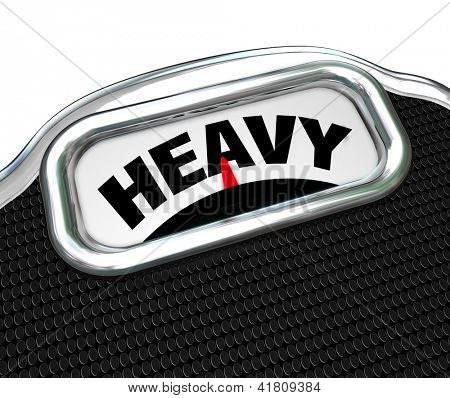 The word Heavy on the display of a scale in close-up, measuring weight or mass to determine if you are overweight and need to diet to improve your health and lose weight