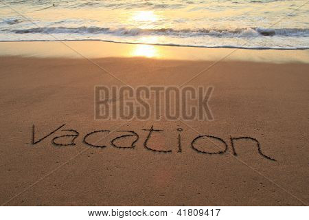 Vacation written in the sand on a sunset beach.