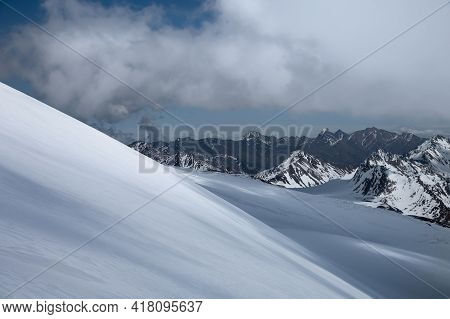 An Untouched Snow Slope High In The Caucasus Mountains Against The Backdrop Of Snow-capped Peaks And