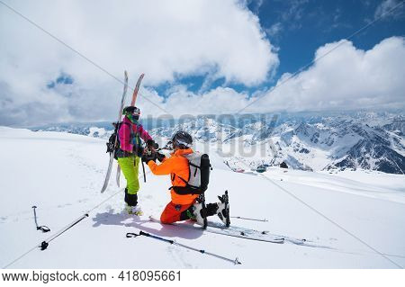 A Young Male Skier Stands On His Knee Inviting His Beloved Girlfriend, A Skier, To Become His Wife H
