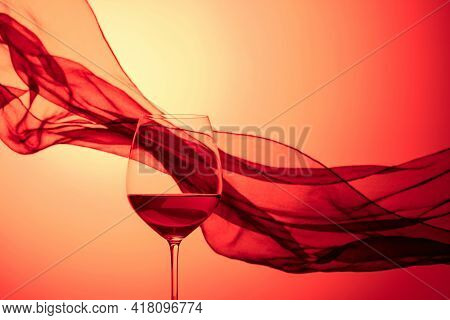 Glass Of Red Wine On A Background Of Waving Black Satin Curtain. Red Backlit.