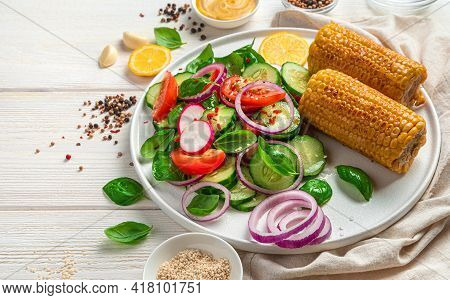 Fresh Vegetable Salad And Roasted Corn On A Light Background With Spices, Basil And Lemon. Vegetaria