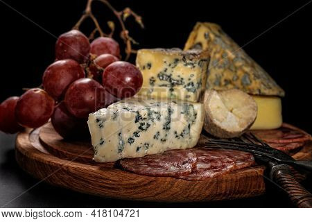 Food Still Life. Assorted Various Gourmet Cheeses, Raw Smoked Sausages And Large Sweet Grapes On A D