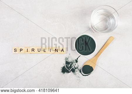 Spirulina Powder In A Spoon On A Gray Table, Top View, Hard Light, Heart, Inscription Spirulina