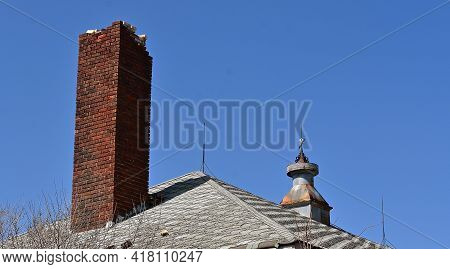 Crumbling Chimney, Old Lightning Rods, And Cupola On The Roof Of A Vacant Building.