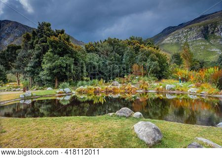 Landscape of Beautiful Lake over Majestic Mountains Covered with Fresh Greenery Background. Harold Porter National Botanical Garden. South Africa.