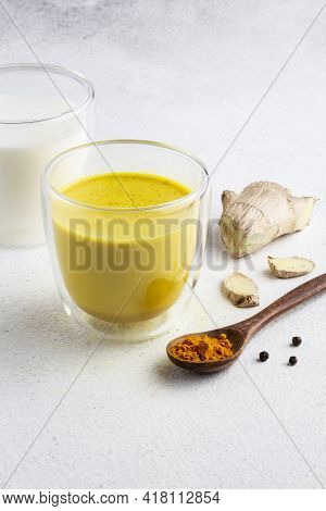Golden Milk With Turmeric Powder In Glass Over White Background, Copy Space. Health And Energy Boost