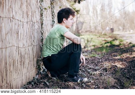 Guy Is A Teenager Sitting At A Fence In The Park And Dreams Of A Good Blessed Future. The Teenager H