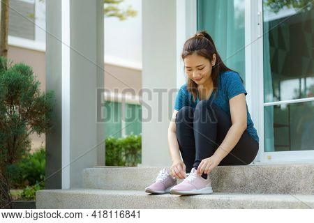 Asian Woman Are Wearing Shoes On The Front Steps Of Their Homes To Jogging In The Neighborhood For D