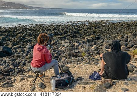 People Wantching And Photographing Surfers At La Santa On Lanzarote Island In Spain
