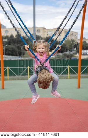 Cute Caucasian Child Girl Swinging On A Swing On A Children's Playground