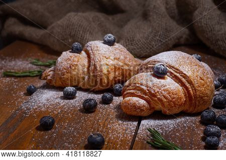 Tasty Baked Croissants With Raw Blueberry And Powdered Sugar On Old Brown Wooden Table And Burlap Cl