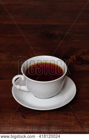 A White Cup And Saucer On A Brown Wooden Table, Breakfast In Solitude. Copy Space
