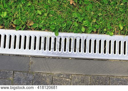 Drainage System Separates The Grass And The Paved Sidewalk. Sewerage And Grate On The Ground For Wat